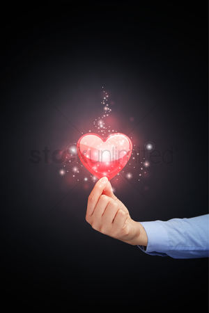 Heart shapes : Hand holding a sparkling heart shape