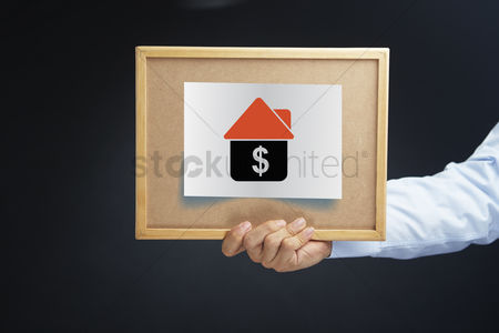 Dollar sign : Hand holding board with dollar sign in a house