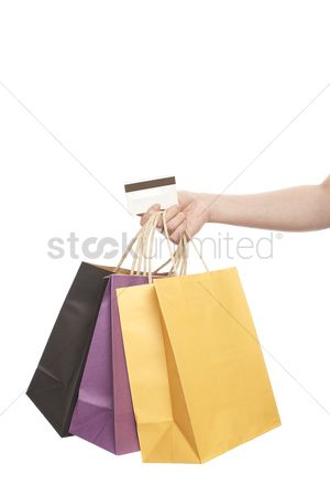 Shopping background : Hand holding credit card with shopping bags