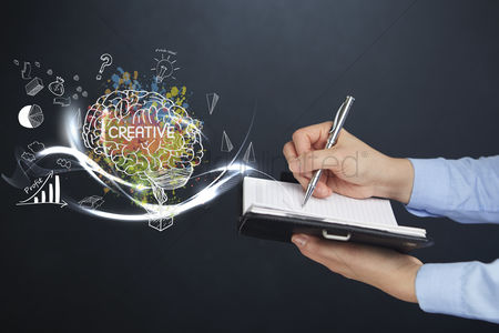 Media : Hand holding notebook and pen with creative concept