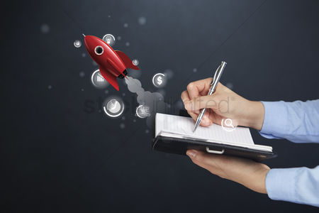 Media : Hand holding notebook and pen with startup concept