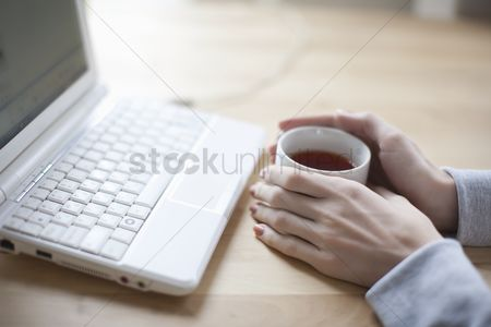 Technology : Hand holds a cup of black tea and laptop keyboard