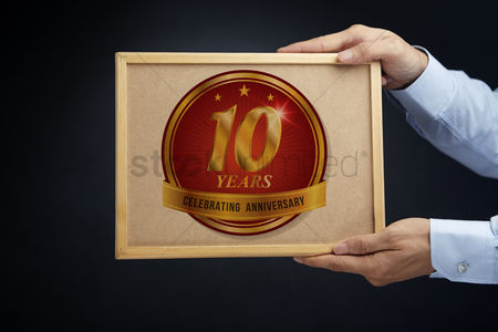 Cork board : Hands holding a board with 10 years anniversary label