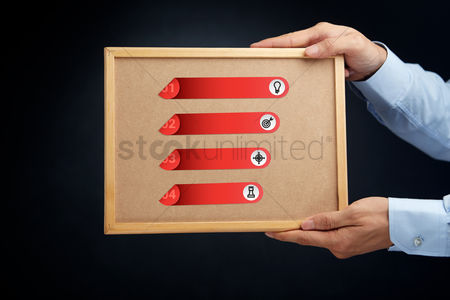 Cork board : Hands holding a cork board with business infographic elements