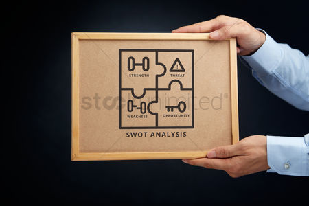 Cork board : Hands holding a cork board with swot analysis concept