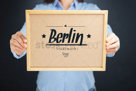 Cork board : Hands holding cork board with berlin trademark concept