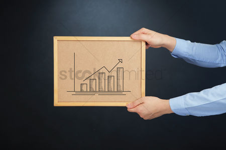 Cork board : Hands holding cork board with business graph concept
