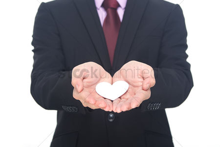 Heart shapes : Hands offering a heart shaped paper