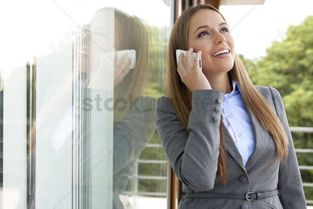 Cell phone : Happy businesswoman answering cell phone by glass door