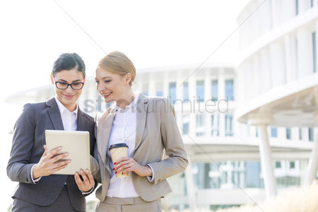 People : Happy businesswomen using digital tablet outside office building