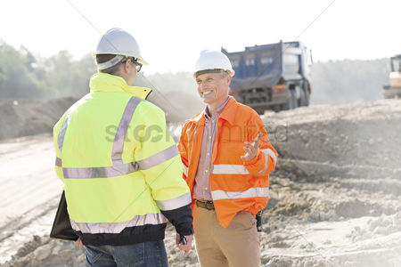 Supervisor : Happy engineer talking to colleague at construction site on sunny day