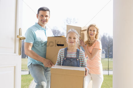 Three quarter length : Happy family with cardboard boxes entering new home