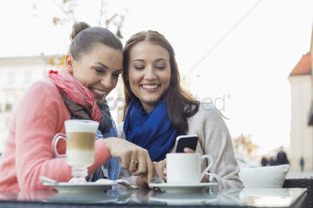 Women : Happy female friends using cell phone at sidewalk cafe