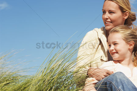 Grass : Happy mother and daughter sitting together in long grass against blue sky