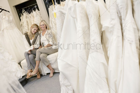 Fashion : Happy mother and daughter sitting together on sofa in bridal boutique