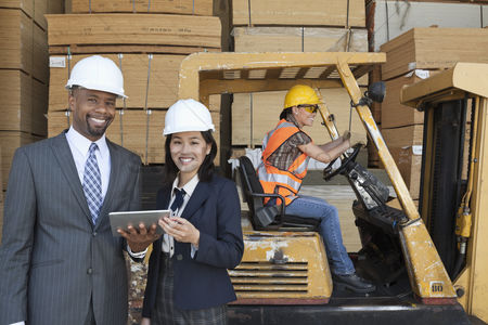 Forklift : Happy multiethnic engineers holding tablet pc with female worker driving forklift truck in background