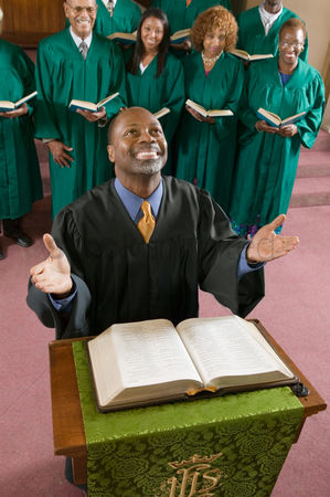 Religion : Happy preacher with bible at church altar looking up high angle view