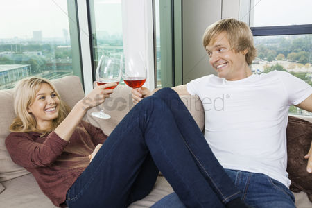 Toasting : Happy relaxed couple toasting wine glasses in living room at home