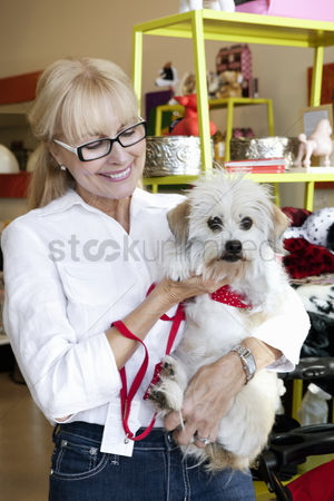 Large group of animals : Happy senior woman carrying dog in pet shop