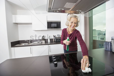 Senior women : Happy senior woman cleaning kitchen counter