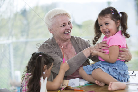 Hispanic : Happy senior woman having quality time with granddaughters at home