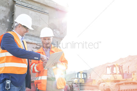 Supervisor : Happy supervisors discussing over clipboard at construction site against clear sky