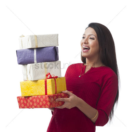 Housewife : Happy woman holding stack of gifts and smiling
