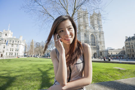 Religion : Happy woman using cell phone against westminster abbey in london  england  uk