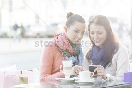 Two people : Happy women using cell phone at sidewalk cafe during winter