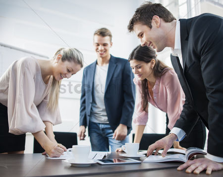 Three quarter length : Happy young business people brainstorming at conference table