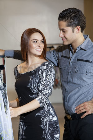 Selection : Happy young couple looking at each other while shopping in fashion boutique