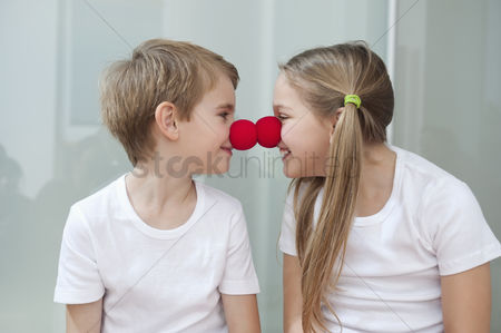 Czech republic : Happy young siblings in white tshirts rubbing clown noses against each other