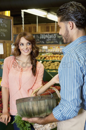 Supermarket : Happy young woman looking at store clerk in supermarket
