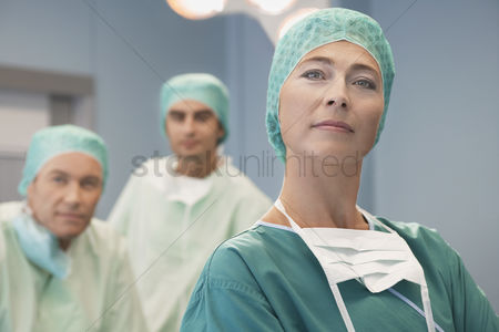 Leadership : Head of surgical team with surgeons in operating theatre portrait