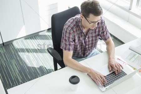 Women : High angle view of businessman using laptop at desk in creative office