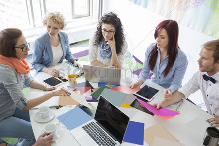 Women : High angle view of businesspeople analyzing photographs in creative office