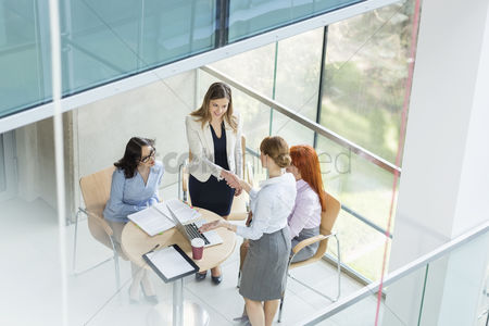 Women : High angle view of businesswomen shaking hands at table in office