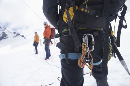Rope : Hiker s back with backpack and safety rope in snowy mountains with two friends ahead back view