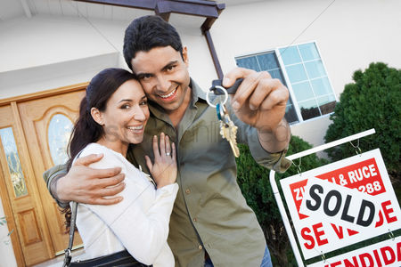 Smiling : Homeowners standing in front of house with sold sign holding key portrait