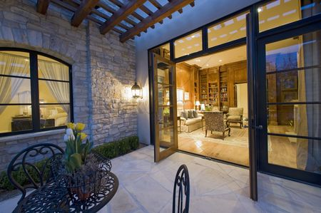 Furniture : House exterior at night with some patio furniture and open patio doors looking into the lit interior