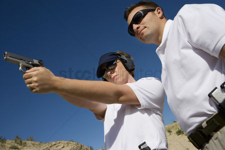 Firing : Instructor assisting woman aiming hand gun at firing range low angle view