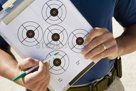 Firing : Instructor holding clipboard with target diagram mid section