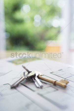 First : Key ring with three keys lying on architectural blueprints close-up