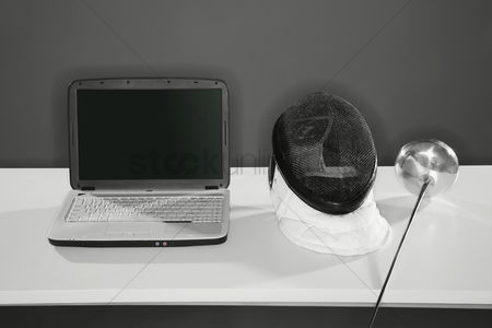 Fight : Laptop with fencing mask and foil on the table