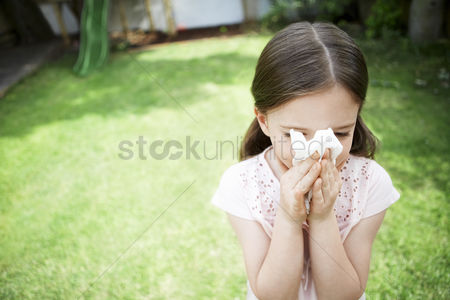 Cold : Little girl in backyard blowing nose close up
