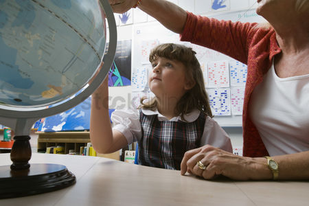 Teacher : Little girl learning geography