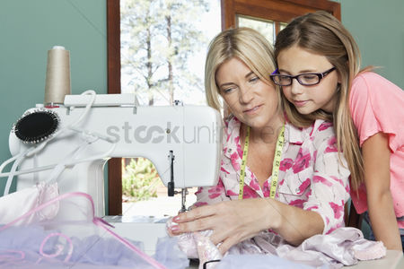 Pre teen : Little girl looking at mother sewing cloth