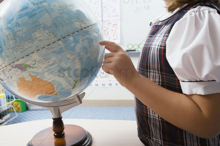 School children : Little girl pointing to globe
