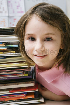 Schoolkids : Little girl with a stack of books