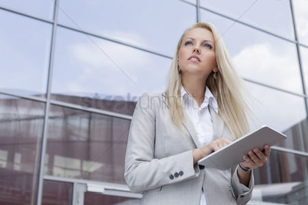 Employee : Low angle view of businesswoman holding digital tablet while looking away against office building